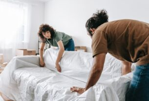 A man and a woman relocating a couch before long-distance moving